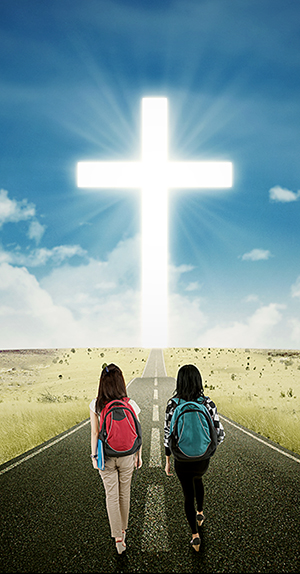 Two students walking toward a cross
